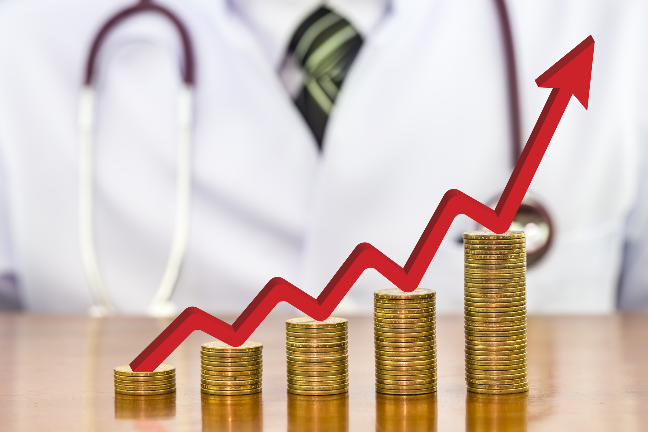 Red arrow over stack of money coins arranged as a graph on wood table with blurry the doctor stethoscope around neck a scene in the back, concept of financial health